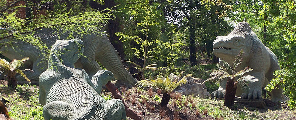 Three life-size sculptures of dinosaurs.