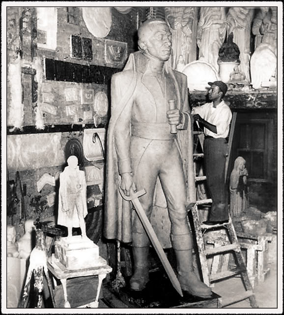 A man working on the Toussaint L'Ouverture sculpture
