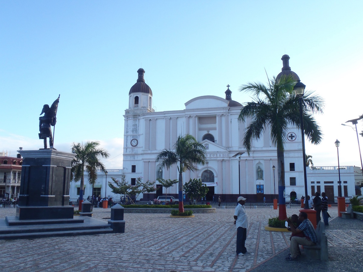Place d'Armes in Cap-Haïtien, featuring a statue and a large building.