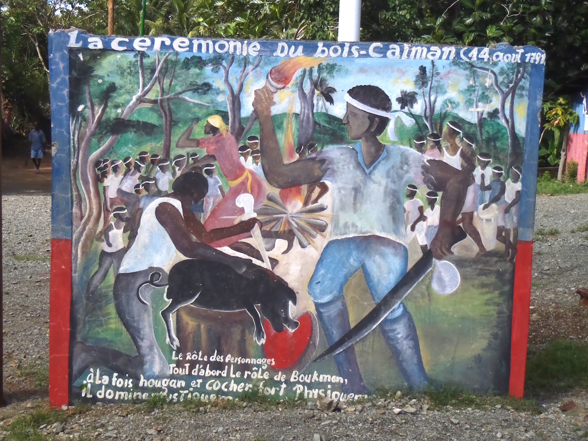 Mural representing two men killing a pig in front of a crowd.