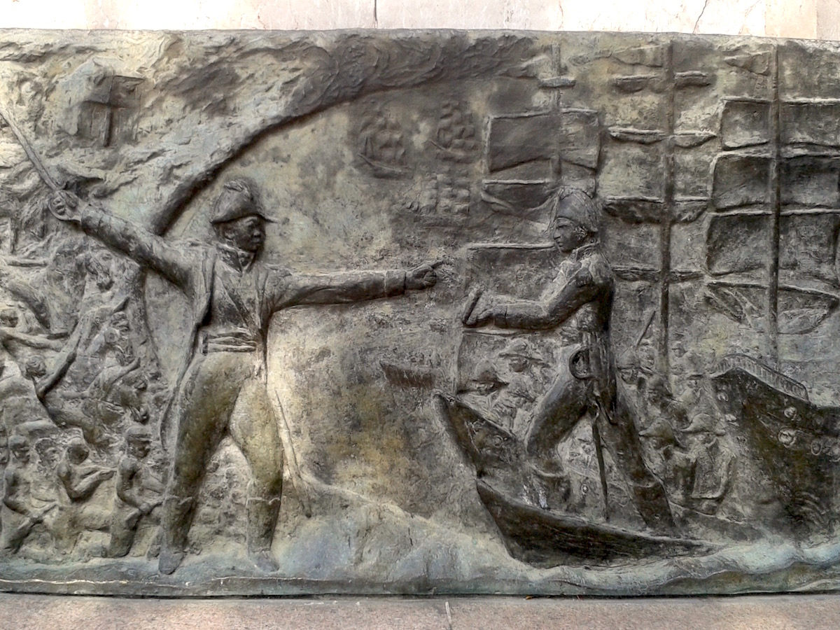 Sculpture of a man on a ship being greeted by another man with a sword.