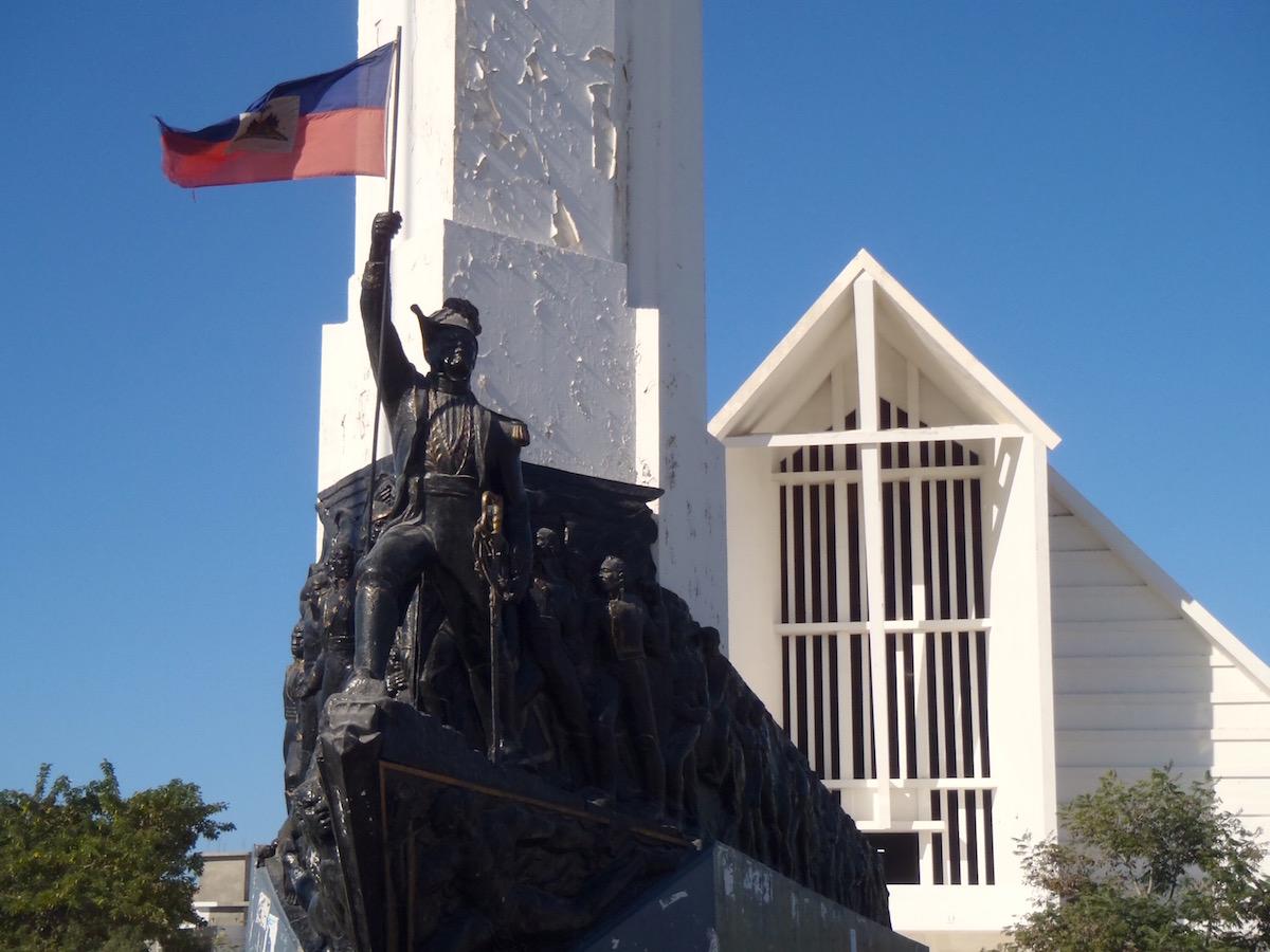 Sculpture of Dessalines holding a Haitian flag.