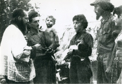 Enrique Ermus at a baptism, with woman and man holding children.