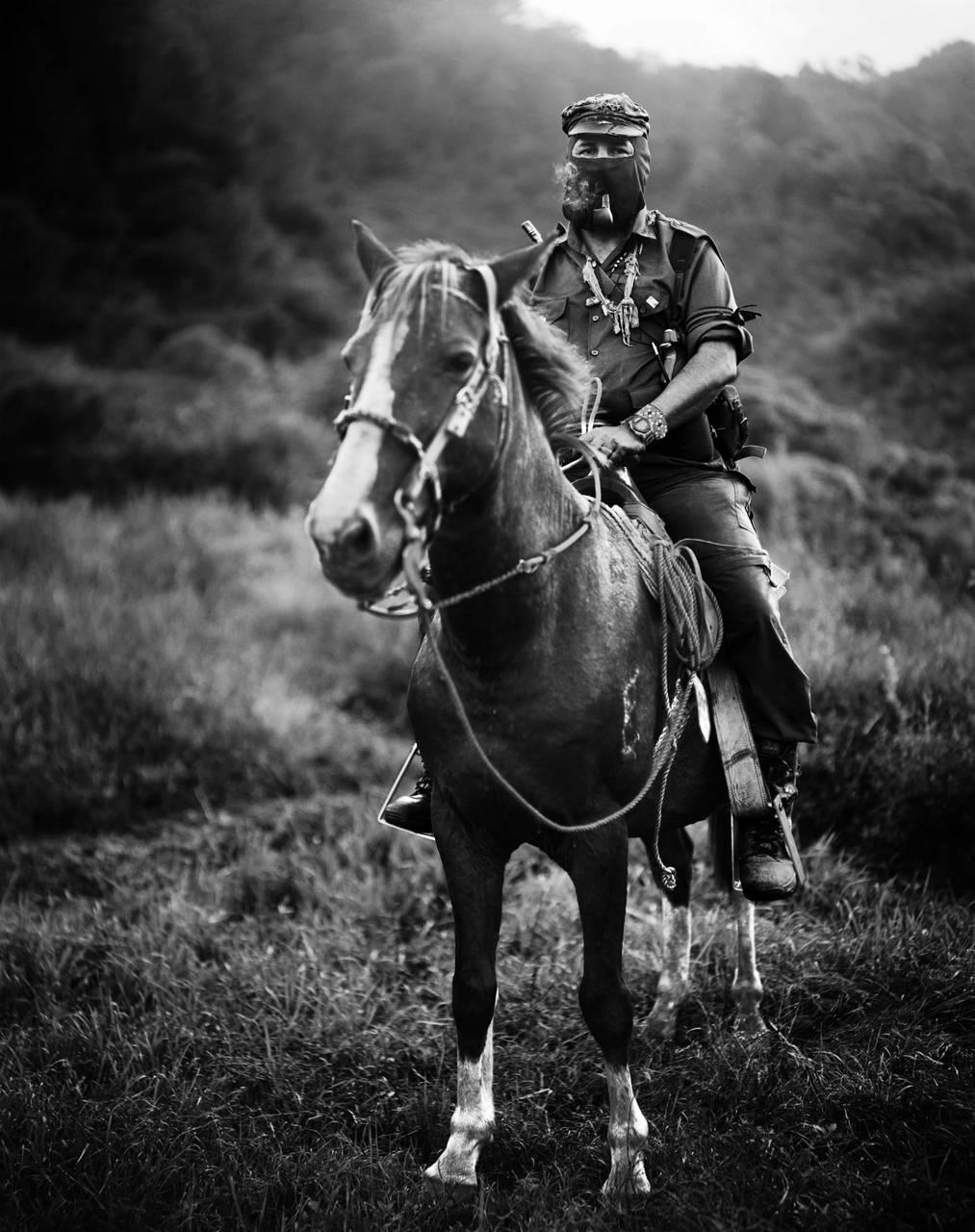 Photograph of a man riding a horse.