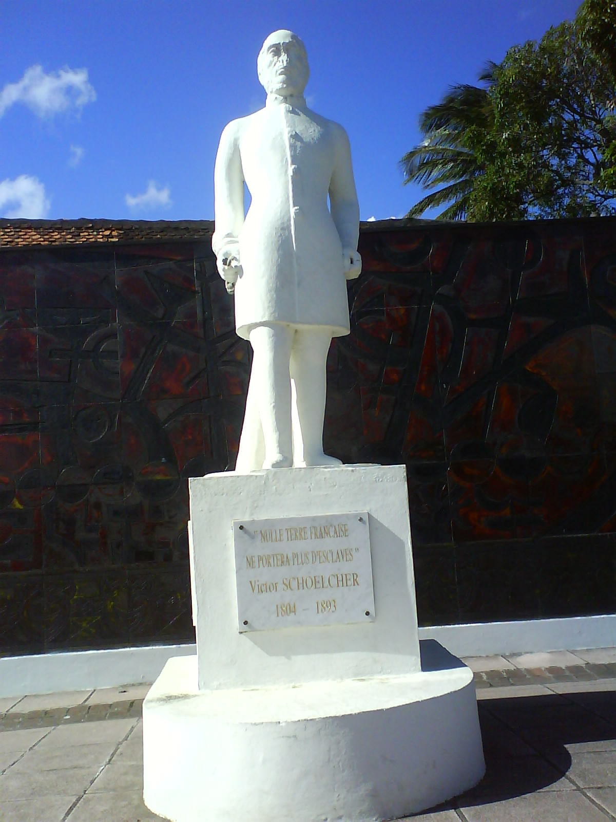 Statue of Victor Schoelcher in white stone, standing up.