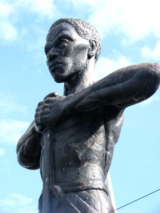 Statue of Paul Bogle standing up with his hands on his chest.