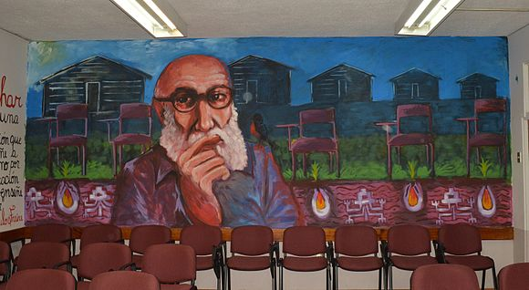 Mural of Paulo Freire in front chairs and houses.