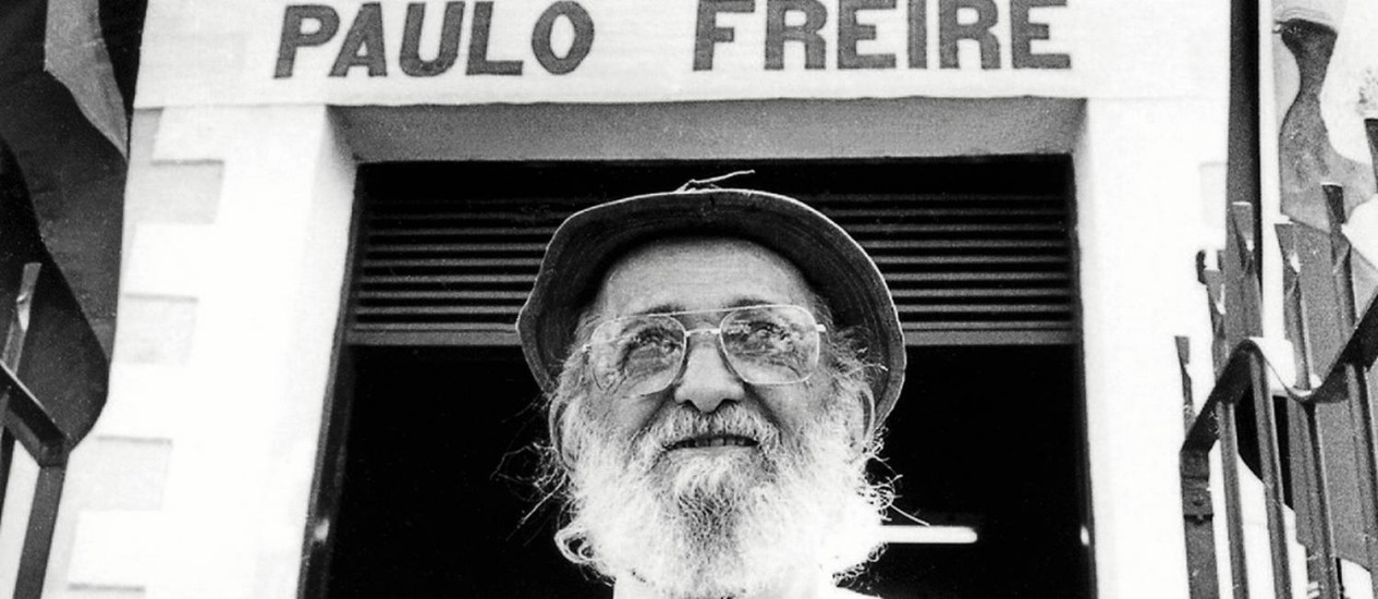 Picture of Paulo Freire in front of a building with his name on it.