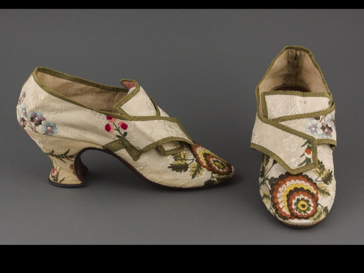 A pair of women's shoes from the 1770s, with heels and flower embroidery.