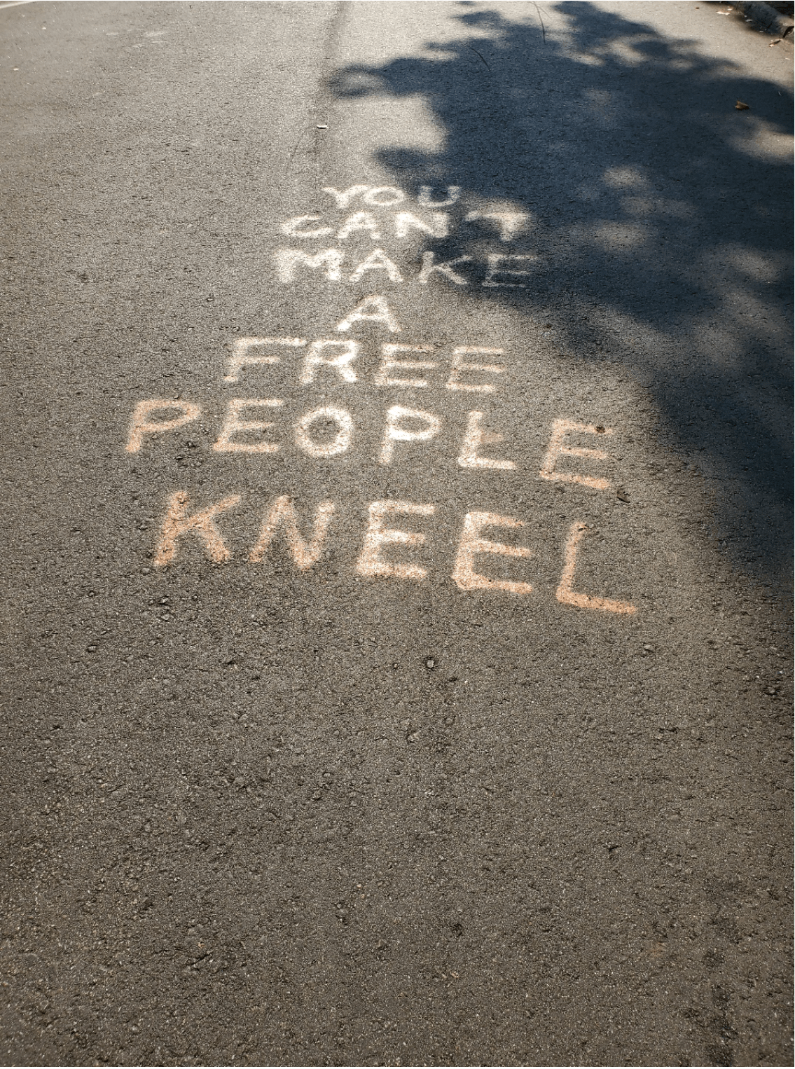 "Graffiti on the road that reads ""You can't make a free people kneel."""
