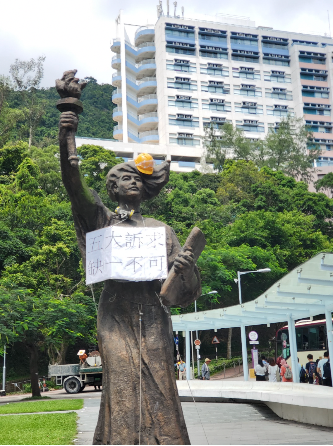 Statue wearing a worker helmet and a cardboard sign around her neck with Chinese characters.