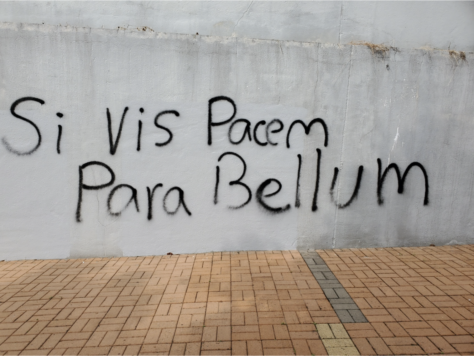 "Graffiti on a wall that reads ""If you want peace, prepare for war"" in Latin."