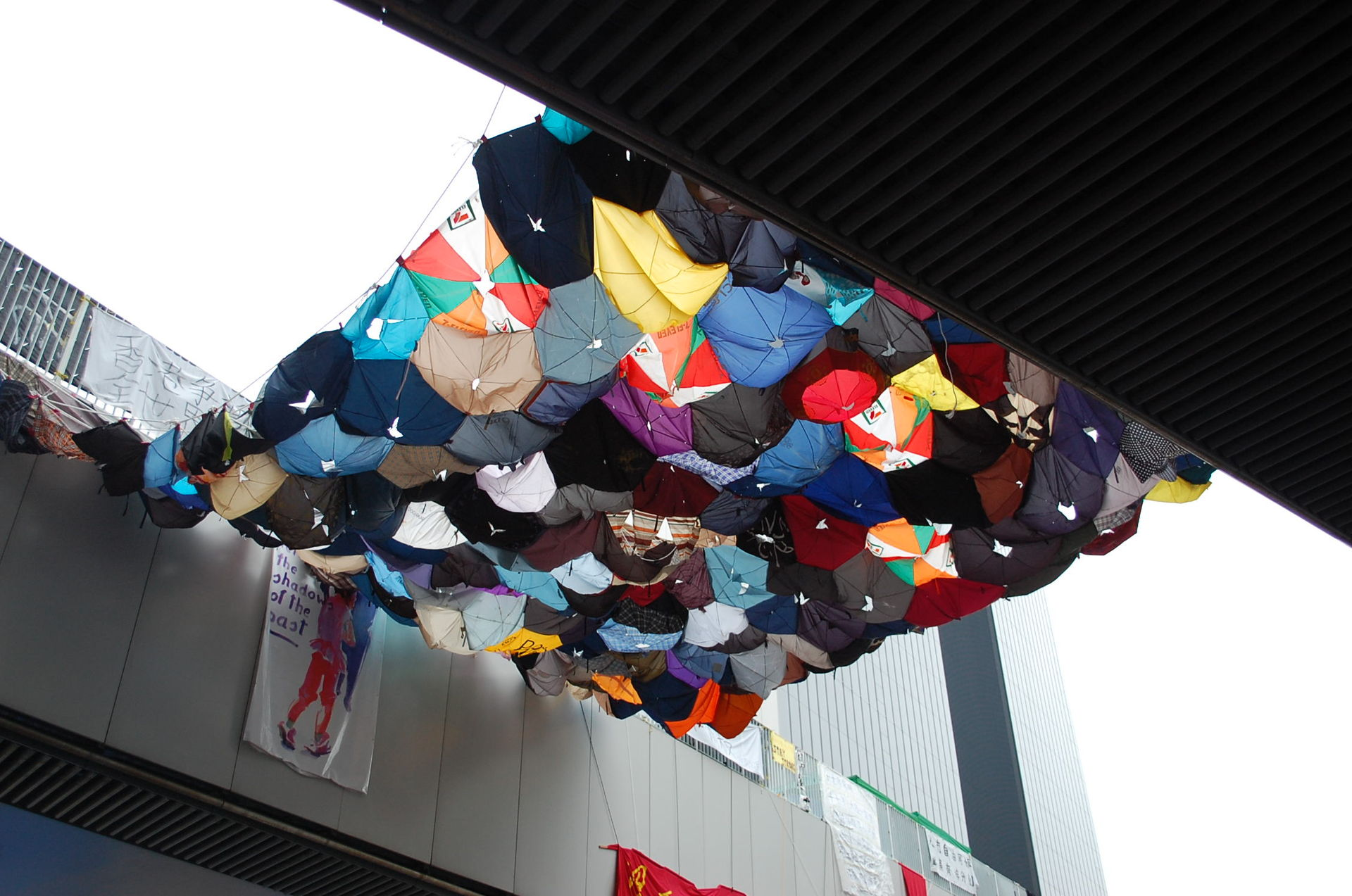 Umbrellas hanging between two footbridges in Hong Kong.