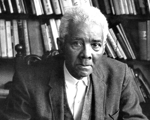 Black and white photograph of C.L.R. James sitting in front of bookshelves.