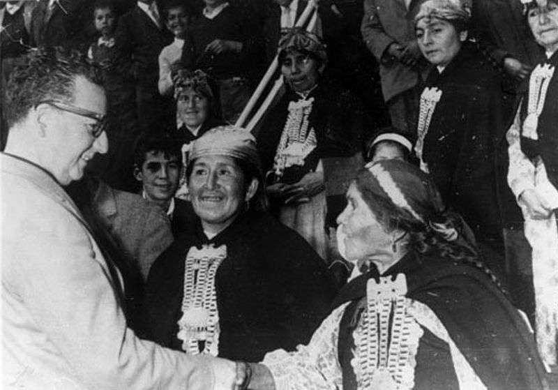 Photograph of Salvador Allende shaking hands with a Mapuche woman.