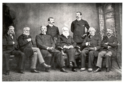 The seven executive officers of the American Historical Association sitting in a row with two standing in the back, posing for a photograph.