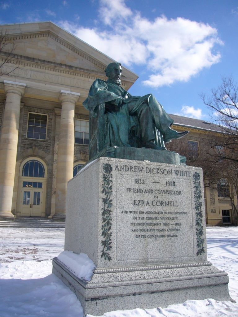 Statue of Andrew Dickson White sitting in a chair, in front a building at Cornell university.