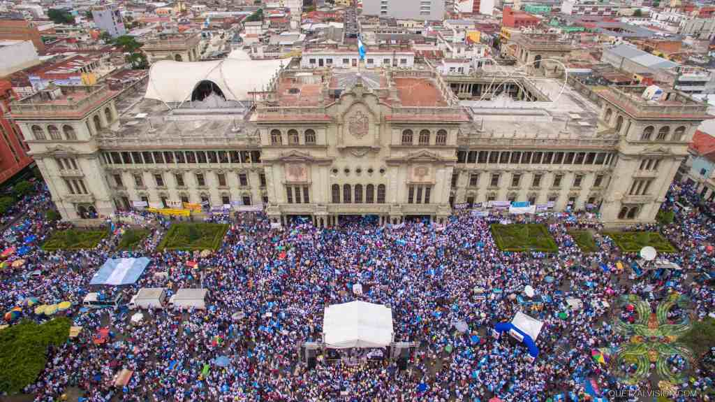 A crowd protesting in front of Guatemala's Presidential Palace.