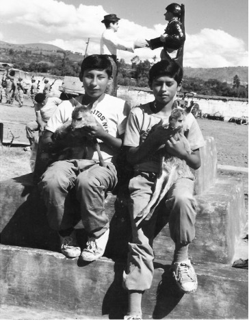 Two boys sitting and holding small animals.